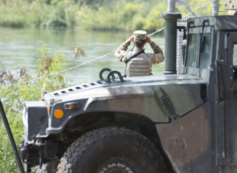 This April 10, 2018 photo provided by the Texas Military Department shows a soldier from the Texas National Guard scanning the shores of the Rio Grande in Starr County, Texas as part of the federal call-up to the U.S.-Mexico border. (Sgt. Mark Otte/Texas Military Department via AP)