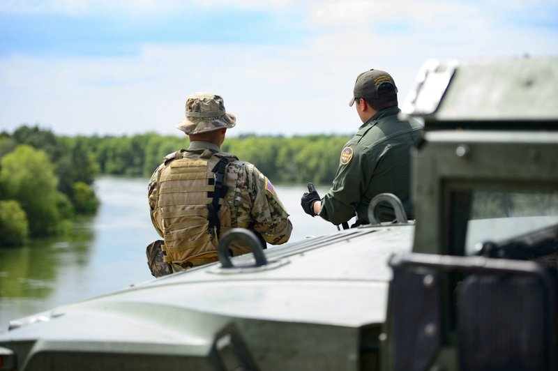 This April 10, 2018 photo provided by the Texas Military Department shows a Texas Guardsman and a U.S. Border Patrol agent discussing the lay of the land along the Rio Grande in Starr County, Texas, as part of the federal call-up to the U.S.-Mexico border. (Sgt. Mark Otte/Texas Military Department via AP)
