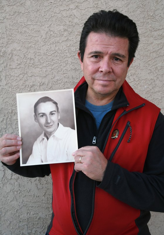 This Tuesday, Oct. 30, 2018, photo provided by Reuben Ortiz, shows Reuben Ortiz holding a photo of the Rev. Jerome Coyle in Albuquerque, N.M. Ortiz says he was angered to learn that Coyle, who had been living at his home until recently, admitted in 1986 that he sexually abused 50 Iowa boys and that the church has kept it quiet for decades. (Tania Ortiz/Reuben Ortiz via AP)