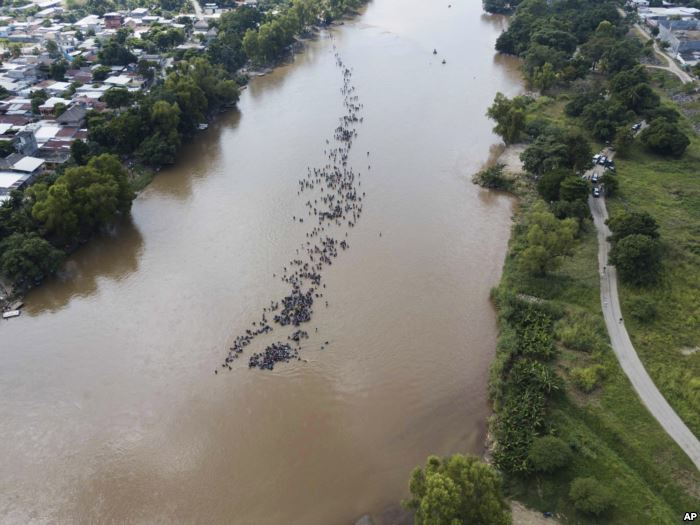 A new group of Central American migrants bound for the U.S border wade in mas