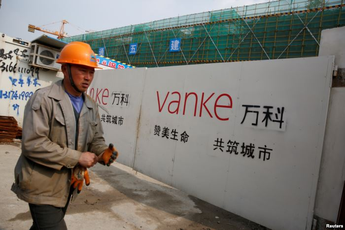 A person walks past by a gate with a sign of Vanke at a construction site in