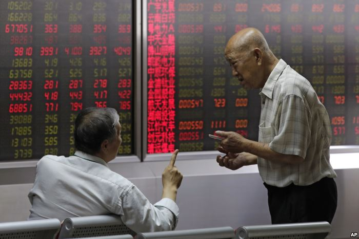 FILE - People chat as they monitor stock prices at a brokerage house in Beiji