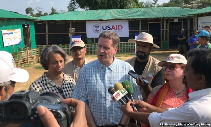FILE - USAID Administrator Mark Green, center, speaks to reporters at the Bal