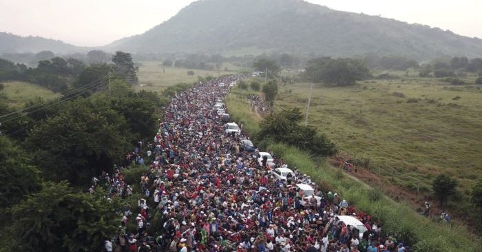 Members of a US-bound migrant caravan stand on a road after federal police briefly blocked their way outside the town of Arriaga, Saturday, Oct. 27, 2018. (Photo: AP)