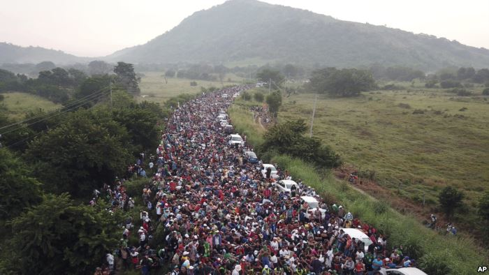 Members of a US-bound migrant caravan stand on a road after federal police br