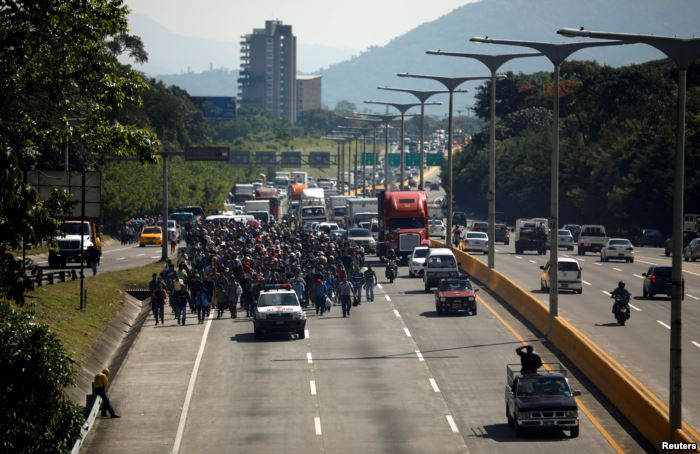 People walk in a caravan of migrants departing from El Salvador en route to t