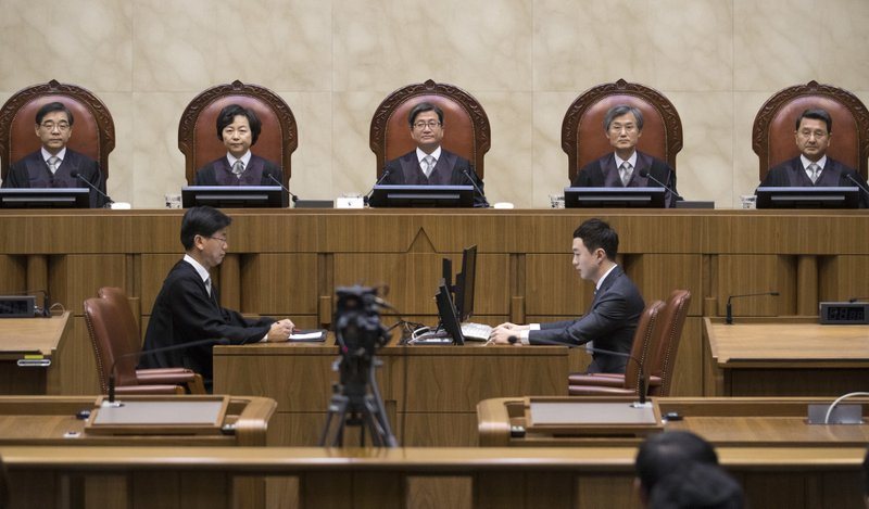 South Korean Chief Justice of the Supreme Court Kim Myeongsu, center, sits with other justices upon their arrival at the Supreme Court in Seoul, South Korea, Thursday, Nov. 1, 2018. South Korea's top court has ruled that people can legally reject mandatory military service on conscientious or religious grounds and must not be punished. (Yun Dong-jin/Yonhap via AP)