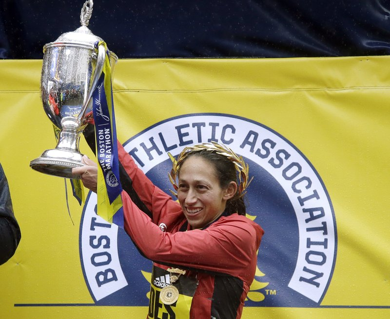 FILE- In this April 16, 2018, file photo, Desiree Linden, of Washington, Mich., hoists the trophy after winning the women's division of the 122nd Boston Marathon on in Boston. Shalane Flanagan last year became the first American woman in 40 years to win the NYC Marathon. Desiree Linden followed with a victory in Boston. All of which motivates Molly Huddle for Sunday's race in New York, who was third there in 2016 in her marathon debut. (AP Photo/Elise Amendola, File)