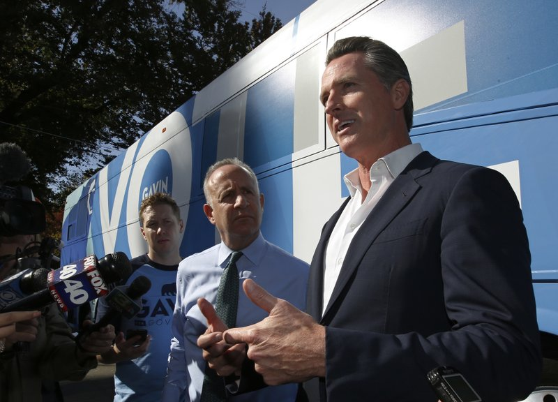 Lt. Gov. Gavin Newsom right, the Democratic candidate for governor, talks with reporters after his visit to the Penleigh Child Development Center, Wednesday, Oct. 31, 2018, in Sacramento, Calif. The stop was part of a statewide bus tour in the days leading up to the Nov. 6 election. Newsom, is running against San Diego area businessman John Cox, a San Diego, a Republican. At left is Sacramento Mayor Darrell Steinberg. (AP Photo/Rich Pedroncelli)