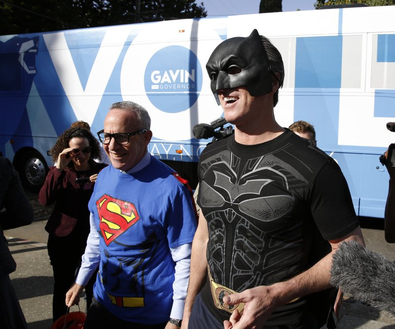 Lt. Gov. Gavin Newsom, right, the Democratic candidate for governor, got in the Halloween spirit dressing up as Batman during his visit to the Penleigh Child Development Center, Wednesday, Oct. 31, 2018, in Sacramento, Calif. The stop was part of a statewide bus tour in the days leading up to the Nov. 6 election. Newsom is running against San Diego area businessman John Cox, a San Diego, a Republican. At left is Sacramento Mayor Darrell Steinberg. (AP Photo/Rich Pedroncelli)