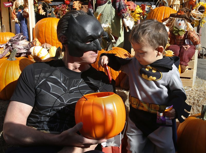 Ezekel Miner, 2, takes some candy from California Lt. Gov. Gavin Newsom, both dressed as Batman, during Newsom's Halloween visit to the Penleigh Child Development Center, Wednesday, Oct. 31, 2018, in Sacramento, Calif. Newsom the Democratic candidate for governor, is starting a statewide bus tour for the final days leading up to the Nov. 6 election. (AP Photo/Rich Pedroncelli)