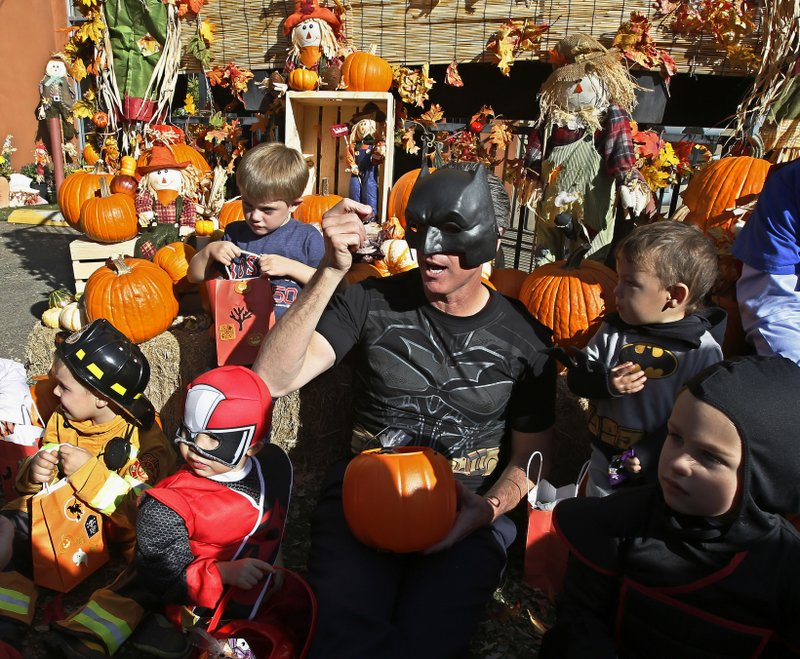 Getting into the Halloween spirit, Lt. Gov. Gavin Newsom, dressed as Batman, hands out Halloween treats to costumed children during his visit to The Penleigh Child Development Center, Wednesday, Oct. 31, 2018, in Sacramento, Calif Newsom the Democratic candidate for governor, is starting a statewide bus tour for the final days leading up to the Nov. 6 election. Newsom is running against Republican John Cox, a San Diego area businessman. (AP Photo/Rich Pedroncelli)