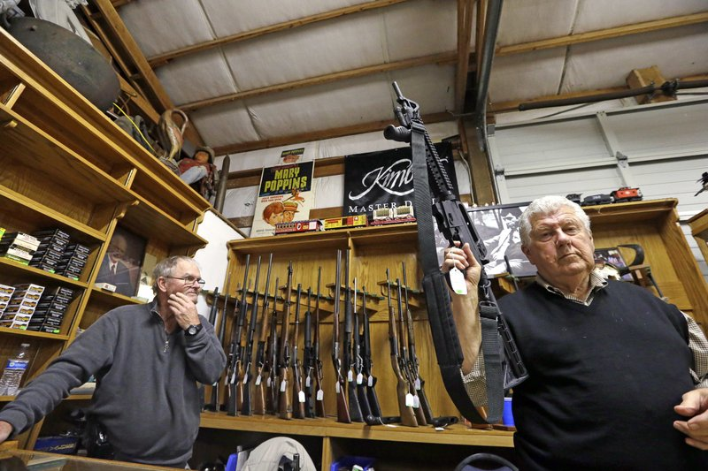 FILE - In this Oct. 20, 2017 file photo, sales clerk Tom Wallitner holds up a Mossberg 715T .22-caliber semi-automatic rifle during an auction at Johnny's Auction House in Rochester, Wash. The Spokane City Council is considering a proposal to prohibit the police department from selling forfeited firearms, following an Associated Press investigation that found that more than a dozen guns sold by law enforcement agencies in Washington state ended up in new police investigations. (AP Photo/Elaine Thompson, File)