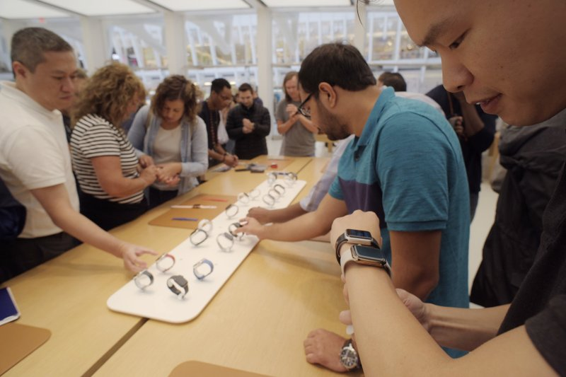 FILE- In this Sept. 21, 2018, file photo customers look at new Apple watches including the Series 4 at an Apple store in New York. Apple Inc. reports earnings Thursday, Nov. 1. (AP Photo/Patrick Sison, File)