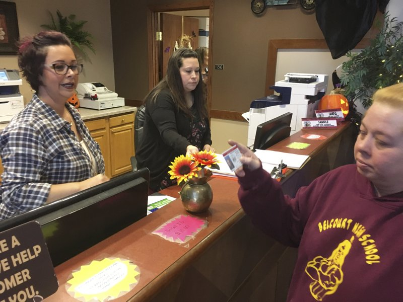 FILE - In this Oct. 24, 2018, file photo, Delaine Belgarde, right, shows the new Turtle Mountain Band of Chippewa identification card she received free of charge, in Belcourt, N.D. It will allow her to vote in November under recently tightened state voter ID rules. (AP Photo/Blake Nicholson, File)