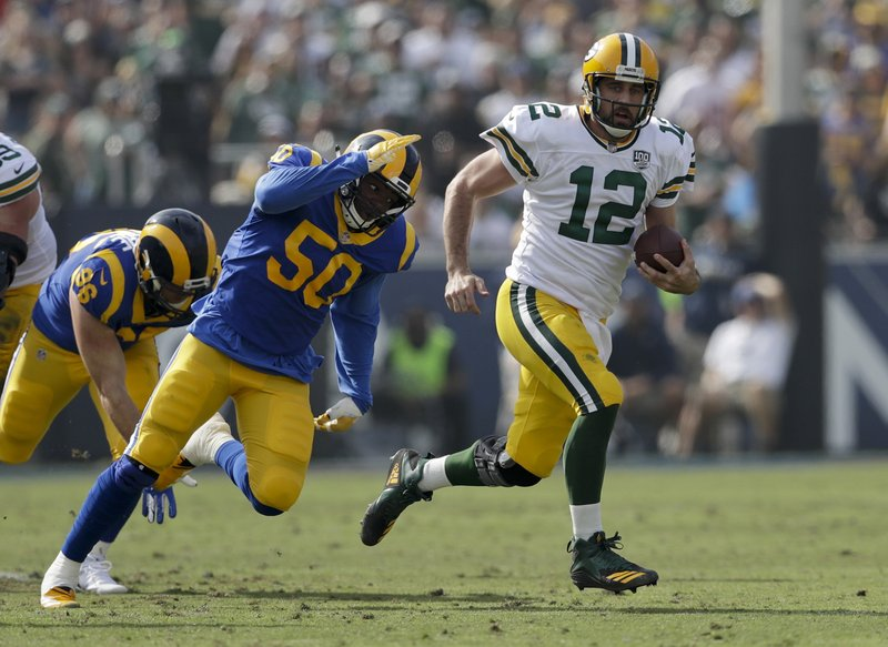 FILE - In this Oct. 28, 2018, file photo, Green Bay Packers quarterback Aaron Rodgers (12) scrambles as Los Angeles Rams linebacker Samson Ebukam (50) defends during the first half of an NFL football game in Los Angeles. Rodgers has been at his MVP form even as the rest of the Packers struggle.