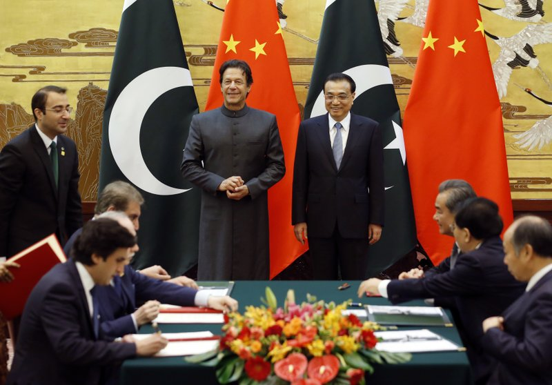Pakistani Prime Minister Imran Khan, center left, and China's Premier Li Keqiang, center right, attend a signing ceremony at the Great Hall of the People in Beijing Saturday, Nov. 3, 2018. (Jason Lee/Pool Photo via AP)
