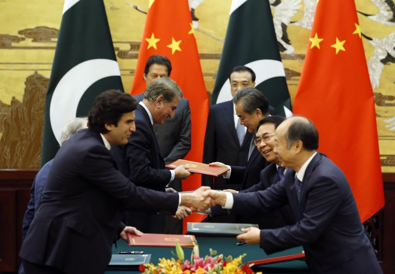 Officials change documents as Pakistani Prime Minister Imran Khan, rear left, and China's Premier Li Keqiang, rear right, attend a signing ceremony at the Great Hall of the People in Beijing Saturday, Nov. 3, 2018. (Jason Lee/Pool Photo via AP)