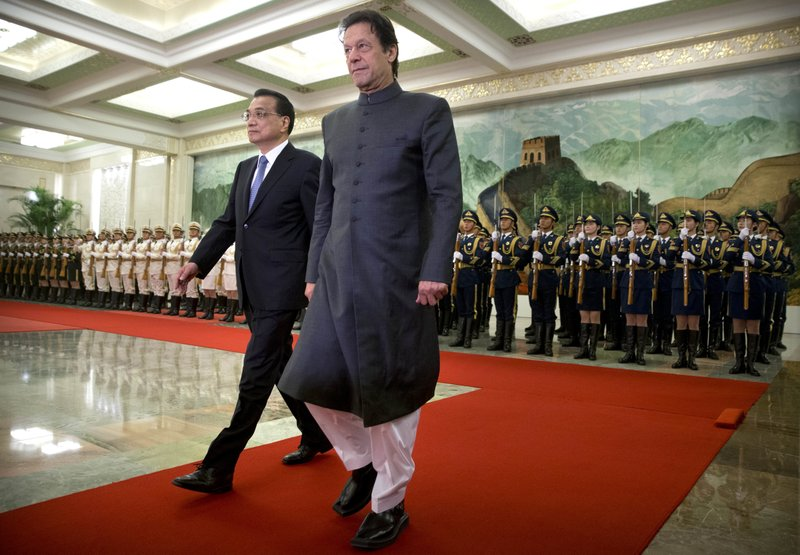 Chinese Premier Li Keqiang, left, and Pakistan's Prime Minister Imran Khan walk together during a welcome ceremony at the Great Hall of the People in Beijing, Saturday, Nov. 3, 2018. (AP Photo/Mark Schiefelbein)