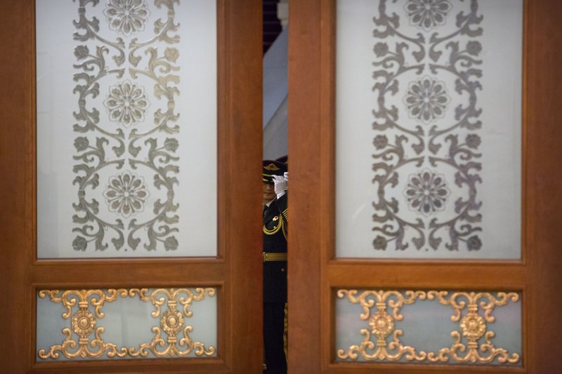 A member of an honor guard adjusts his hat before a welcome ceremony for Pakistan's Prime Minister Imran Khan at the Great Hall of the People in Beijing, Saturday, Nov. 3, 2018. (AP Photo/Mark Schiefelbein)
