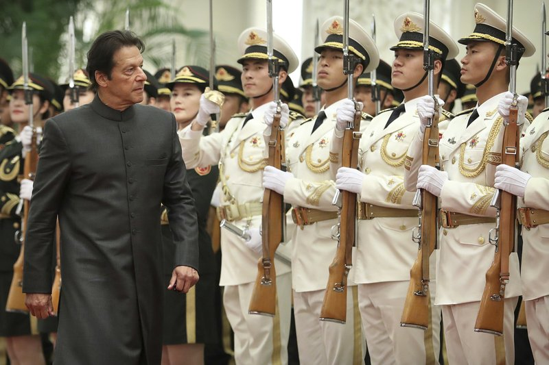 Pakistan's Prime Minister Imran Khan reviews an honor guard during a welcome ceremony at the Great Hall of the People in Beijing, Saturday, Nov. 3, 2018. (AP Photo/Mark Schiefelbein)