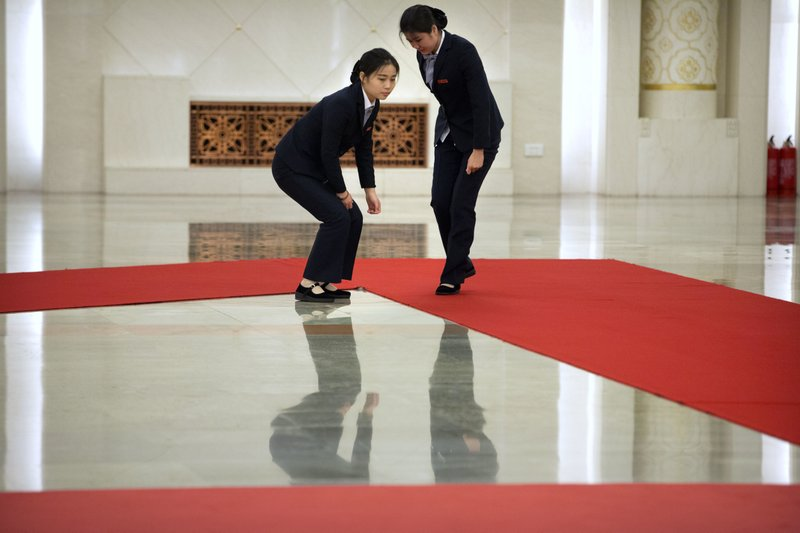 Staff members adjust a red carpet before a welcome ceremony for Pakistan's Prime Minister Imran Khan at the Great Hall of the People in Beijing, Saturday, Nov. 3, 2018. (AP Photo/Mark Schiefelbein)