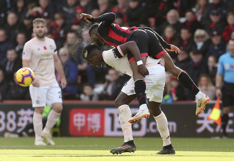 Bournemouth's Jefferson Lerma, bottom, and Manchester United's Paul Pogba battle for the ball during the English Premier League soccer match between Bournemouth and Manchester United at The Vitality Stadium, Bournemouth, England.Saturday Nov. 3, 2018. (Mark Kerton/PA via AP)