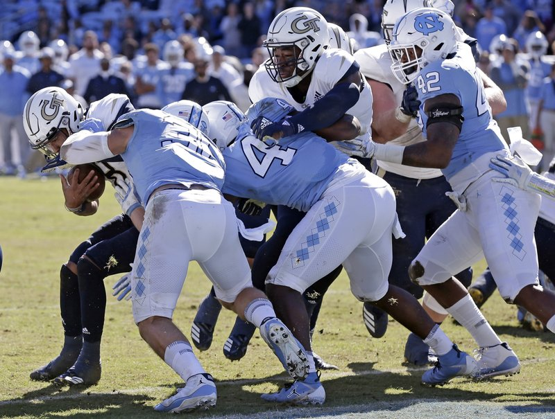Georgia Tech's Tobias Oliver, left, scores a touchdown while North Carolina's Cole Holcomb (36) and Allen Artis (4) try to make the tackle during the first half of an NCAA college football game in Chapel Hill, N.C., Saturday, Nov. 3, 2018. (AP Photo/Gerry Broome)