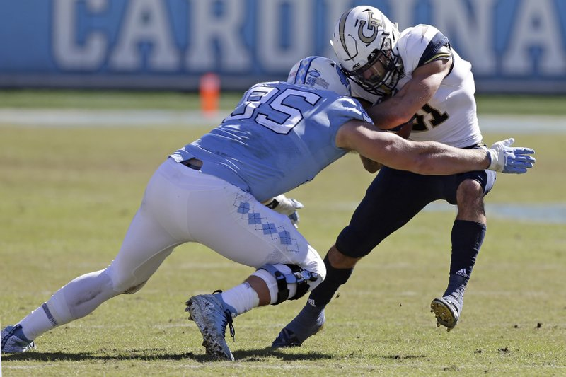 North Carolina's Tyler Powell (95) moves in to tackle Georgia Tech's Nathan Cottrell (31) during the first half of an NCAA college football game in Chapel Hill, N.C., Saturday, Nov. 3, 2018. (AP Photo/Gerry Broome)