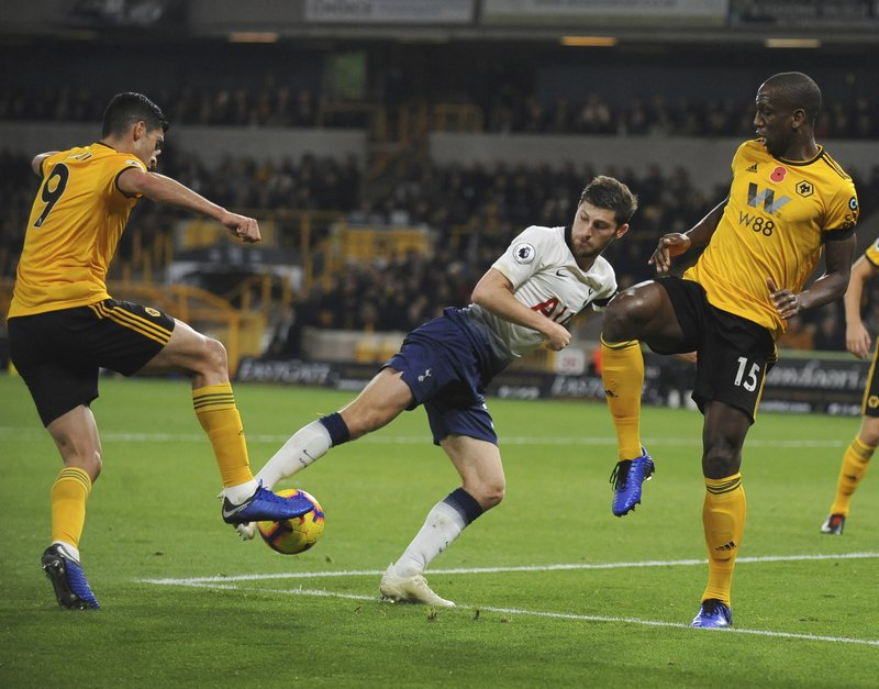 Tottenham's Ben Davies, center, duels for the ball with Wolverhampton's Raul Jimenez, left, and Willy Boly during the English Premier League soccer match between Wolverhampton Wanderers and Tottenham Hotspur at the Molineux Stadium in Wolverhampton, England, Saturday, Nov. 3, 2018. (AP Photo/Rui Vieira)