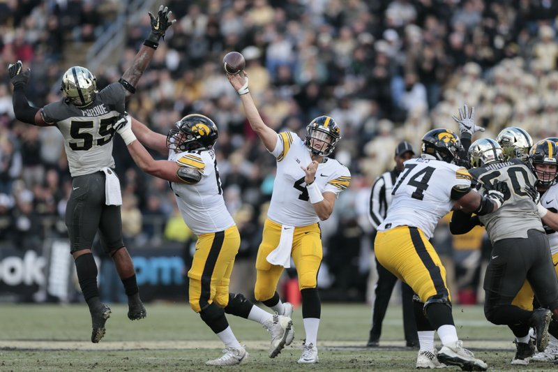 Iowa quarterback Nate Stanley (4) throws a pass as Purdue linebacker Derrick Barnes (55) leaps to defend against it in the first half of an NCAA college football game in West Lafayette, Ind., Saturday, Nov. 3, 2018. (AP Photo/AJ Mast)