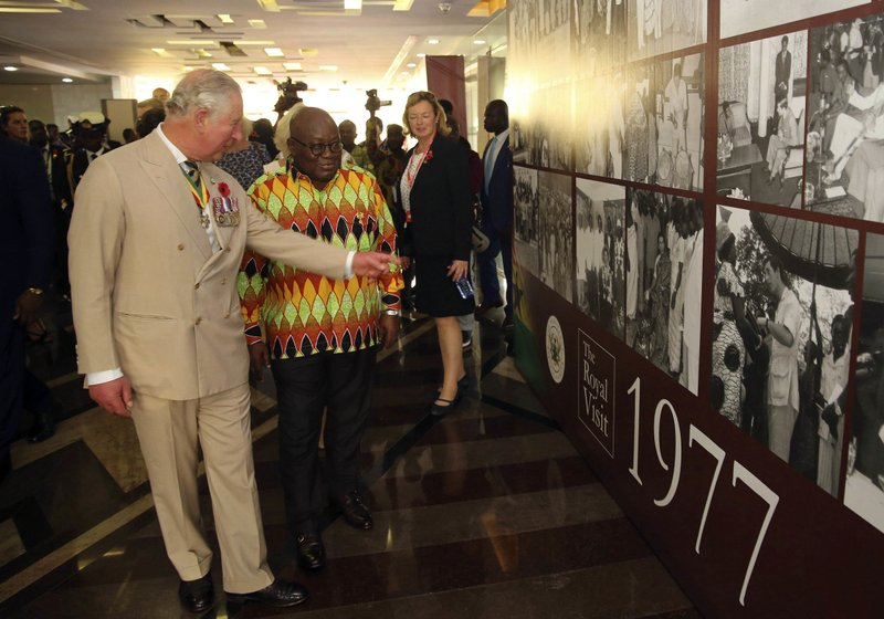 Prince Charles , left and Ghana's President, Nana Akufo-Addo, right, look at memorial photos at the Jubilee House in Accra, Ghana, Friday, Nov. 2, 2018. Prince Charles and his wife Camilla, the Duchess of Cornwall, have arrived in Ghana for the second stop of their West African tour.(AP Photo)