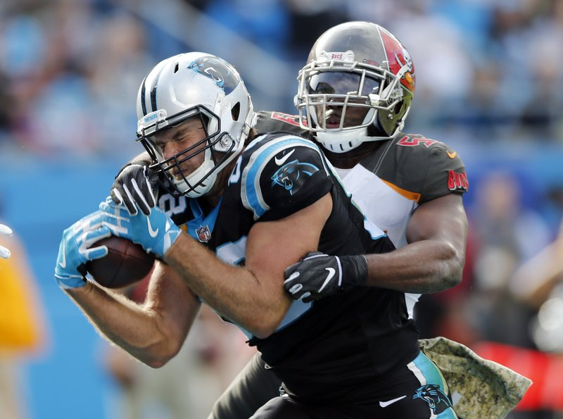 Carolina Panthers' Greg Olsen, left, catches a touchdown pass against Tampa Bay Buccaneers' Adarius Taylor, right, in the first half of an NFL football game in Charlotte, N.C., Sunday, Nov. 4, 2018. (AP Photo/Nell Redmond)