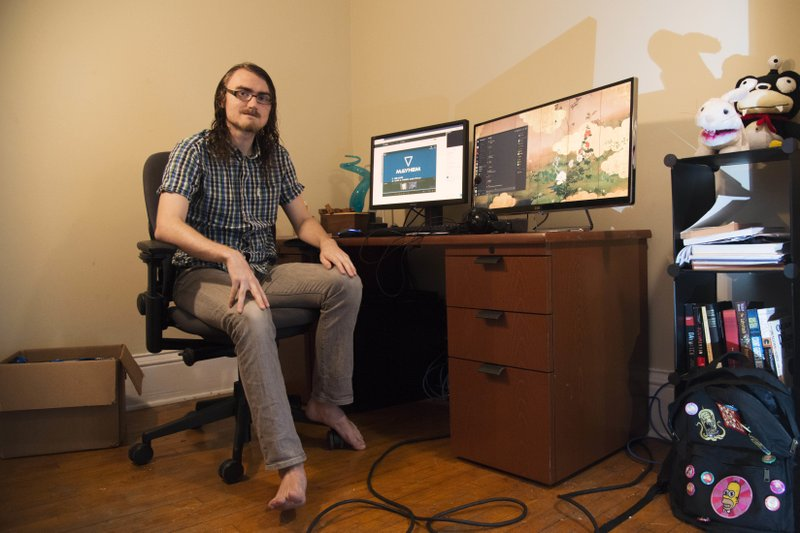 Noah Wrolson poses at his desk before a game of Overwatch with the University ESports team on Sunday, Oct. 28, 2018. Wrolson doesn't play sports, so he said he fills a competitive void by participating in the ESports team. (Jack Rodgers/The Minnesota Daily via AP)