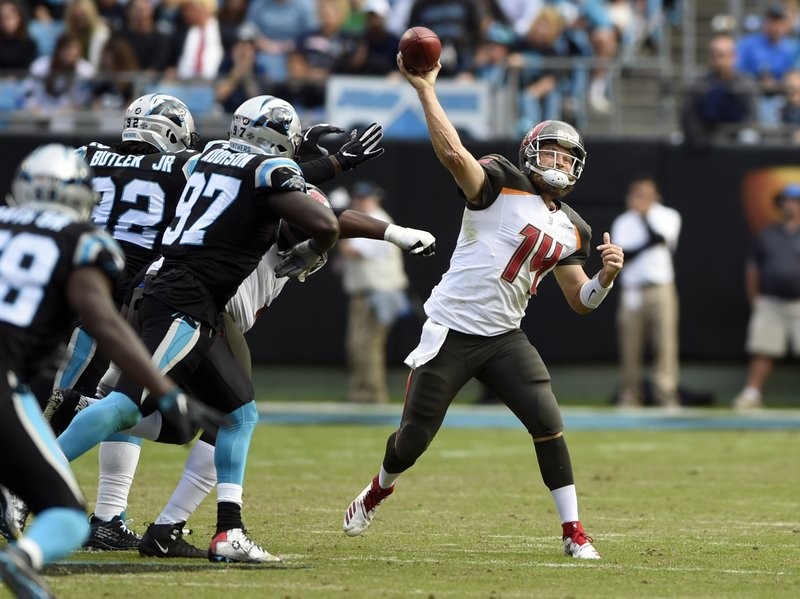 Tampa Bay Buccaneers' Ryan Fitzpatrick (14) throws a pass under pressure from Carolina Panthers' Mario Addison (97) in the first half of an NFL football game in Charlotte, N.C., Sunday, Nov. 4, 2018. (AP Photo/Mike McCarn)