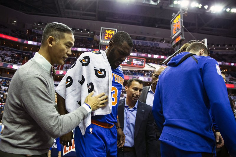 New York Knicks guard Tim Hardaway Jr. (3) is helped off court after falling during the first half of an NBA basketball game against the Washington Wizards, Sunday, Nov. 4, 2018, in Washington. (AP Photo/Al Drago)