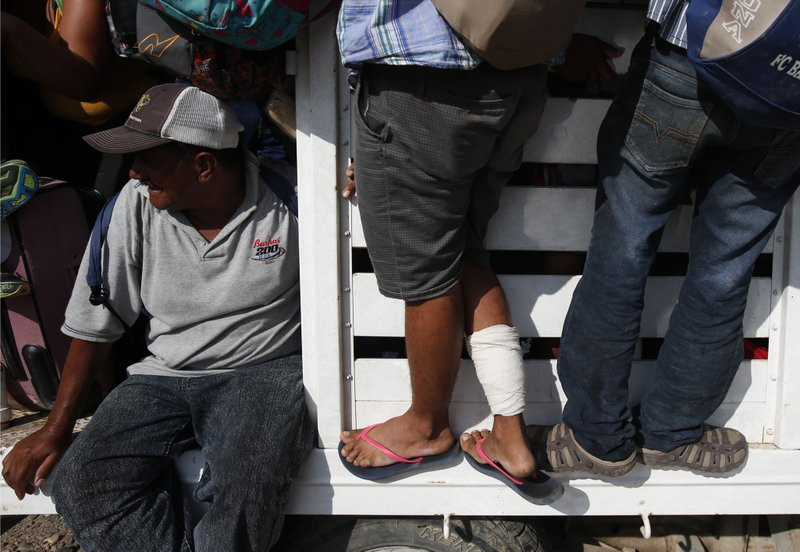 FILE - In this Oct. 29, 2018 file photo, a man who injured his leg by bumping into a pipe while walking in the dark holds on to the outside of a truck, as a caravan of Central Americans continues its slow march toward the U.S. border, in Tapanatepec, Mexico. The most grueling days demand treks of more than 100 miles (160 kilometers), as migrants eager to find strength in numbers must keep that pace to remain with the group. (AP Photo/Rebecca Blackwell, File)
