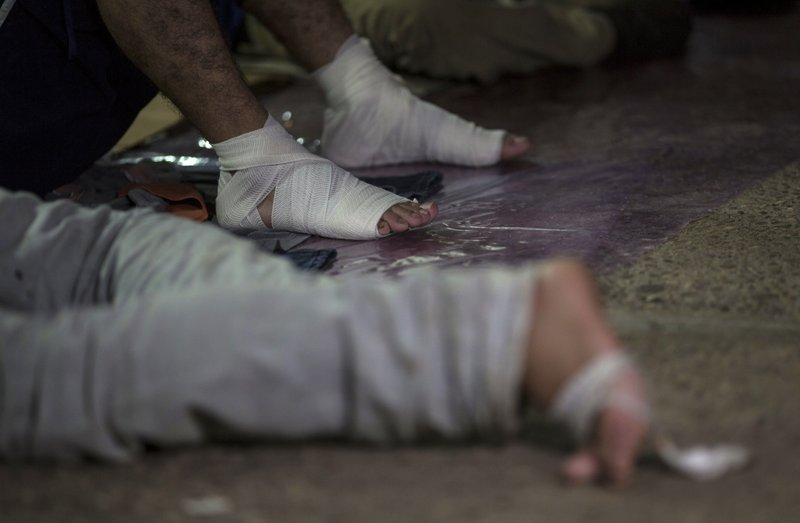 FILE - In this Oct. 26, 2018 file photo, a migrant with bandaged feet rests after walking all day with the U.S.-bound caravan, at a shelter in Arriaga, Chiapas state, Mexico.