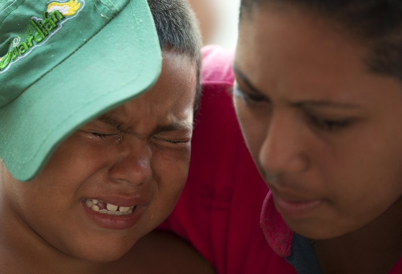 FILE - In this Oct. 26, 2018 file photo, a mother comforts her son as blisters on his feet are treated by Mexican Red Cross volunteers, in Arriaga, Chiapas state, Mexico, as the U.S.-bound migrant caravan stops for the night. Many in the caravan have now covered more than 800 miles since setting out from Honduras on Oct. 13, hitching rides when possible, and face another more than 800-mile trek to the nearest U.S. border crossing. (AP Photo/Rebecca Blackwell, File)