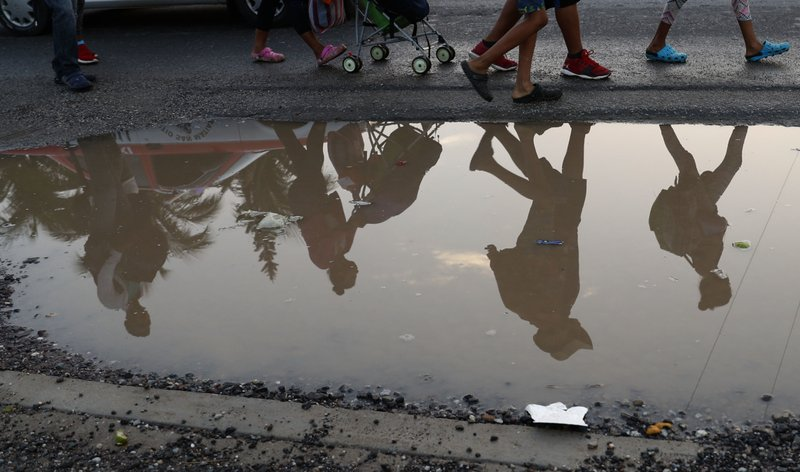 FILE - In this Nov. 2, 2018 file photo, Central American migrants are reflected in water onto side of the road as they begin their morning trek in Donaji, Oaxaca state, Mexico. U.S.-bound migrants walk in cheap shoes and sweat-drenched socks, which they eagerly peel off at the end of each day. (AP Photo/Marco Ugarte, File)