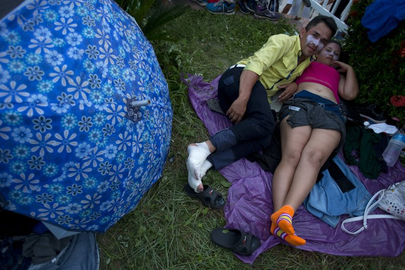 FILE - In this Oct. 25, 2018 file photo, a Honduran couple, who received medical treatment for burned faces and injured feet, rest as a U.S.-bound caravan of Central American migrants stops for the night in Pijijiapan, Chiapas state, Mexico. Blisters are a nasty foe for migrant feet, young and old alike, as Red Cross personnel at way stations bandage swollen feet or apply antiseptic to broken blisters. (AP Photo/Rebecca Blackwell, File)