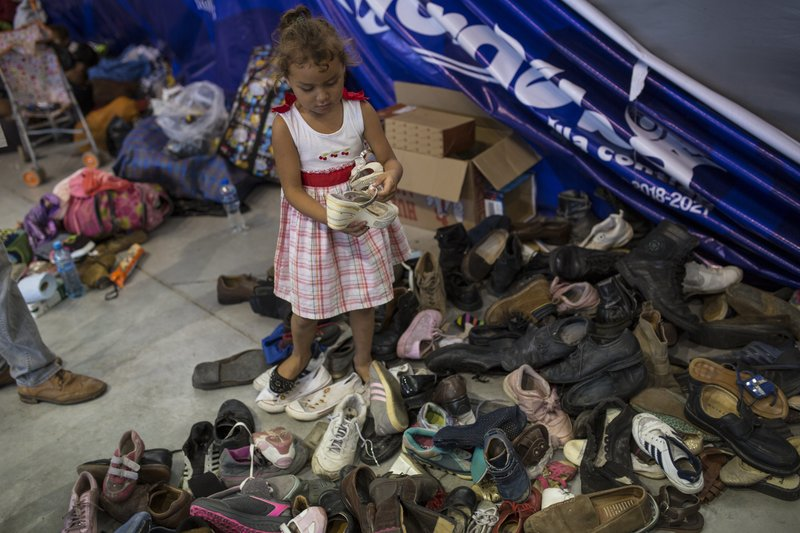 In this Nov. 4, 2018 photo, a girl chooses from donated shoes as members of a U.S.-bound Central American migrant caravan rest at a shelter in Cordoba, Veracruz state, Mexico. The group now finds itself in the Gulf state of Veracruz, traversing what some call the