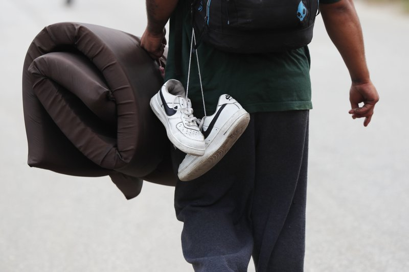 FILE - In this Nov. 3, 2018 file photo, a Central American migrant from the U.S.-bound caravan carries his shoes after a day of walking, in Acayucan, Veracruz state, Mexico. Whenever possible, the migrants discard damaged footwear, replacing them with donated shoes found at stops along the way or with spare pairs they carry in backpacks. (AP Photo/Marco Ugarte, File)