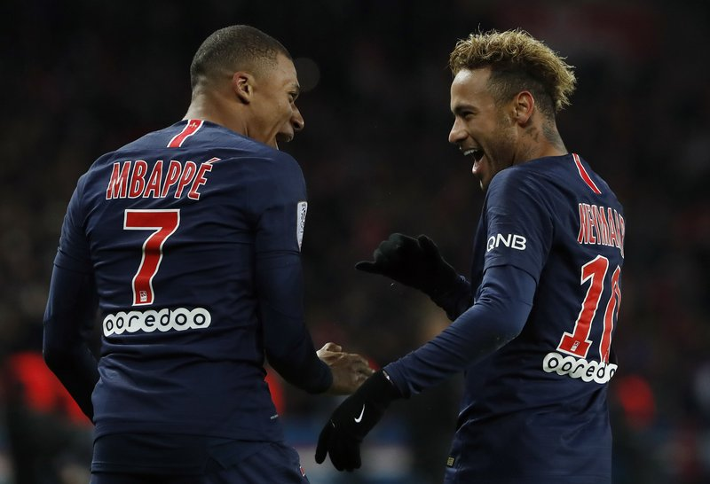 PSG's Kylian Mbappe, left, reacts with PSG's Neymar, celebrating after he scored his side's second goal during the League One soccer match between Paris Saint-Germain and Lille at the Parc des Princes stadium in Paris, Friday, Nov. 2, 2018. (AP Photo/Thibault Camus)