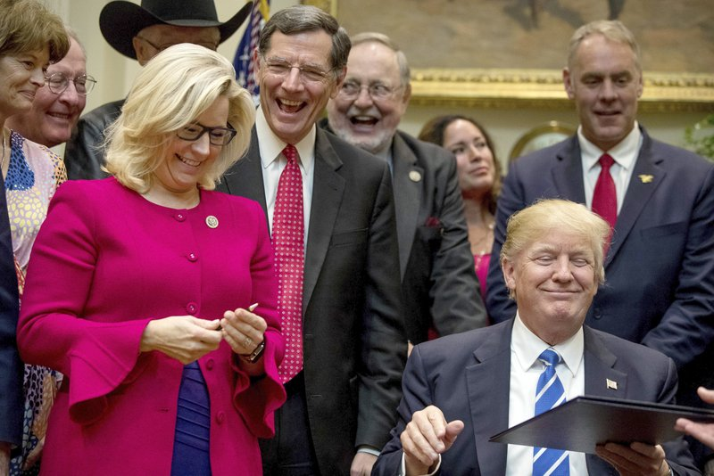FILE - In this March 27, 2017 file photo, President Donald Trump gives his pen to Rep. Liz Cheney, R-Wyo., third from left, after signing one of various bills in the Roosevelt Room of the White House in Washington. From left are, Sen. Lisa Murkowski, R-Alaska, Sen. Lamar Alexander, R-Tenn., Sen. John Barrasso, R-Wyo., Rep. Don Young, R-Alaska and Interior Secretary Ryan Zinke, right, and his wife Lolita, second from right. (AP Photo/Andrew Harnik)