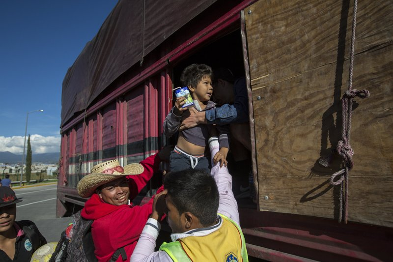 A boy is taken from a truck as Central American migrants arrive at the outskirts of Mexico City, Monday, Nov. 5, 2018. A big group of Central Americans pushed on toward Mexico City from a coastal state Monday, planning to exit a part of the country that has long been treacherous for migrants seeking to get to the United States. (AP Photo/Rodrigo Abd)