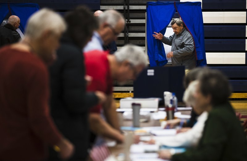 A voter steps from the voting booth after casting his ballot in Doylestown, Pa., Tuesday, Nov. 6, 2018. (AP Photo/Matt Rourke)