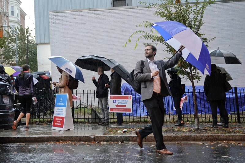 Voters line up in the rain outside Bright Family and Youth Center in the Columbia Heights neighborhood in Washington, Tuesday, Nov. 6, 2018. Across the country, voters headed to the polls Tuesday in one of the most high-profile midterm elections in years.  (AP Photo/Pablo Martinez Monsivais)