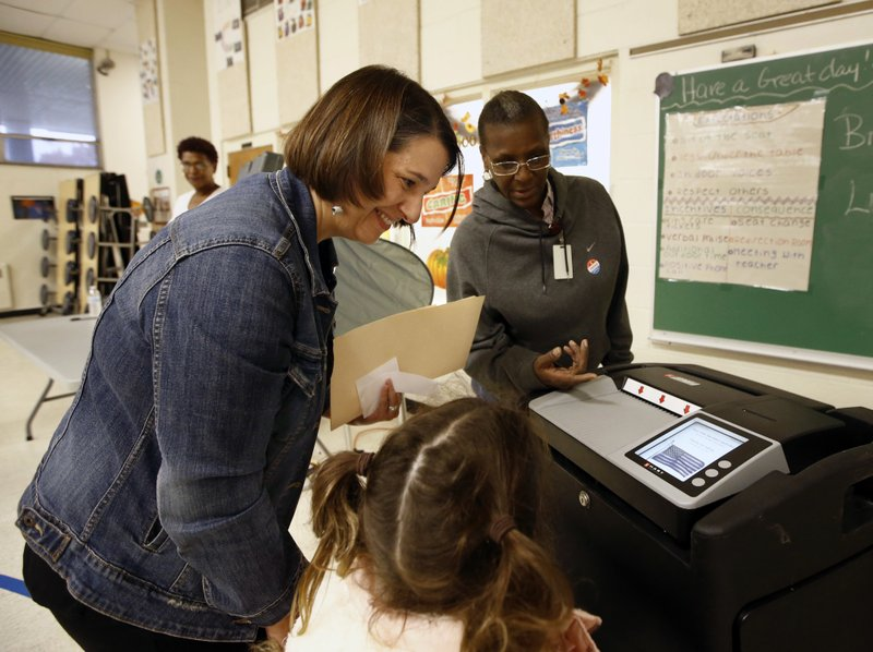 Jess King, left, Democratic nominee for Pennsylvania's 10th congressional district, and her daughter Eleni King-Martin, 9, casts her vote at Martin Luther King Elementary School in Lancaster, Pa., Tuesday, Nov. 6, 2018. (AP Photo/Chris Knight)