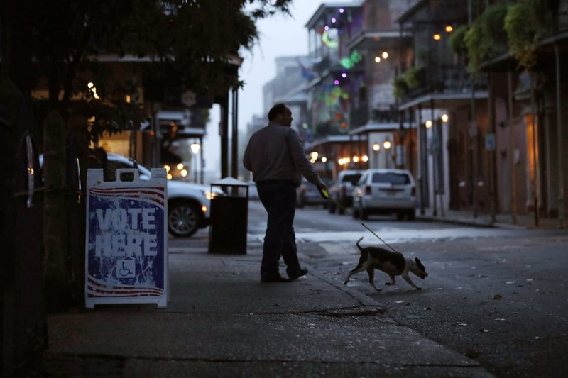 Elliot Scharfenberg walks with his dog as he leaves his polling place after voting in the French Quarter in New Orleans, Tuesday, Nov. 6, 2018. (AP Photo/Gerald Herbert)